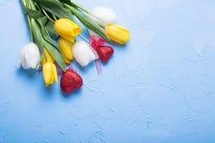 Zwei rote Herzen und gelbe und weiße Tulpen blüht Stockbilder