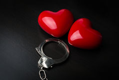 Zwei rote Herzen und Stahlhandschellen auf dunklem Hintergrund St. Valenti Lizenzfreies Stockbild