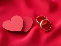 Zwei rote Herzen und zwei Eheringe Lizenzfreies Stockbild
