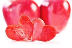 Zwei rote Herzen werden vom Apfel, zwei rote Äpfel auf einem backg herausgeschnitten Lizenzfreie Stockfotografie