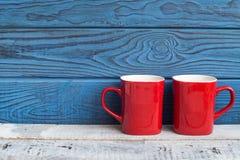 Zwei rote Kaffeetassen auf einem Hintergrund von blauen Brettern Stockfoto