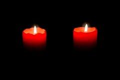 Zwei rote Kerzen, die in der Dunkelheit brennen Stockfotos