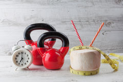 Zwei rote kettlebells mit messendem Band, trinkender Kokosnuss und c Stockbild