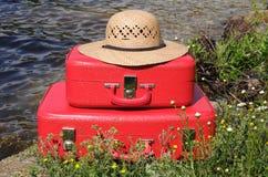 Zwei rote Koffer der Weinlese und Sonnehut Lizenzfreies Stockbild