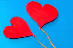 Zwei rote Papierherzen auf blauem Hintergrund Stockbild