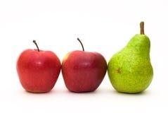 Zwei rote Äpfel und eine grüne Birne Stockbild