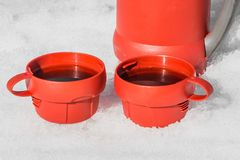 Zwei rote Plastikbecher mit schwarzem heißem Tee mit Dampf und roter Thermosflasche auf einer weißen Schneehintergrundaußenseite  lizenzfreie stockbilder