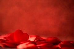 Zwei rote Satinherzen auf rotem Hintergrund-, Valentinsgruß- oder Muttertageshintergrund, Liebesfeiern Stockfotografie