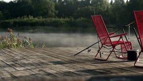 Zwei rote Stühle, die auf Fischenpier auf Hintergrundmorgen stehen, nebeln über Wasser ein stock video footage