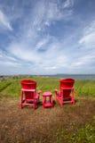 Zwei rote Stühle und Tabelle, die heraus zum Meer schauen Lizenzfreie Stockbilder