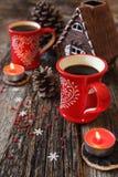 Zwei rote Tasse Kaffees, Kiefernkegel und brennende Kerze Stockfoto