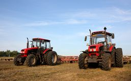 Zwei rote Traktoren mit einer Egge stockfoto