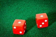 Zwei rote Würfel auf Poker-Tabelle lizenzfreie stockfotos