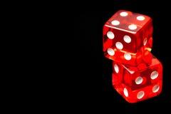 Zwei rote Würfel auf schwarzem Hintergrund Stockbild