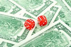Zwei rote Würfel, die auf dem Dollar liegen Lizenzfreies Stockfoto