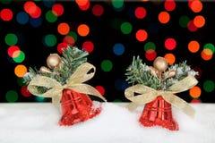 Zwei rote Weihnachtsglocken im Schnee. Stockbilder