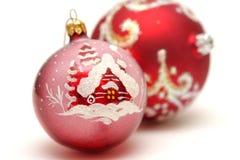 Zwei rote Weihnachtskugeln mit Zeichnung des Hauses Lizenzfreie Stockbilder
