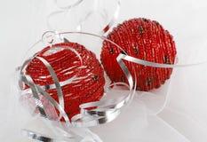 Zwei rote wulstige Weihnachtsverzierungen mit silbernem Farbband Lizenzfreie Stockbilder