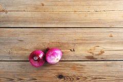 Zwei rote Zwiebeln auf rustikalem hölzernem Hintergrund Lizenzfreies Stockfoto