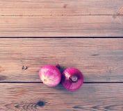 Zwei rote Zwiebeln auf rustikalem hölzernem Hintergrund Lizenzfreie Stockfotografie