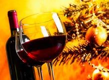 Zwei Rotweingläser nähern sich Flasche gegen Weihnachtsbaumhintergrund Stockbild