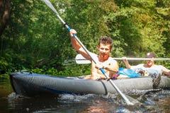 Zwei Ruderer im Boot mit Rudern in den Händen auf dem Fluss am Sommertag Jungesportkerle schwimmen ein Kanu entlang dem Fluss lizenzfreie stockfotos
