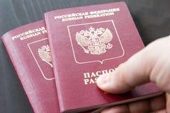 Zwei russische Pässe in der Hand Russische amtliche Urkunde auf dunklem Hintergrund Lizenzfreies Stockbild