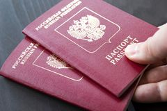 Zwei russische Pässe in der Hand Russische amtliche Urkunde auf hölzernem Hintergrund Lizenzfreies Stockbild