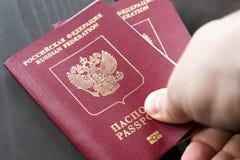 Zwei russische Pässe in der Hand Russische amtliche Urkunde auf hölzernem Hintergrund Lizenzfreie Stockfotografie