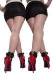 Zwei Sätze der roten Fersen, der Beine und der geohrfeigten Knöchel. Stockfoto