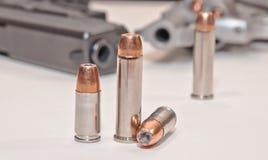 Zwei Sätze der verschiedenen Kugeln mit einem Revolver und einer Pistole im Hintergrund Lizenzfreie Stockfotos