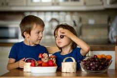 Zwei süße Kinder, Jungenbrüder, frische Früchte zu Hause essend stockfoto
