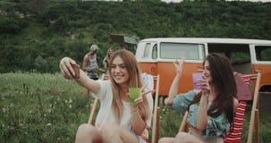 Zwei 90 s-Damen haben eine Picknickzeit mit ihren Freunden, sie sitzen auf den Picknickstühlen, die selfies Trinken nehmen stock video footage