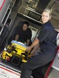 Zwei Sanitäter, die Rollbahre vom Krankenwagen löschen stockbild