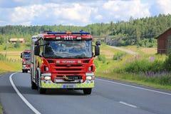 Zwei Scania-Löschfahrzeuge auf der Straße am Sommer Lizenzfreies Stockbild