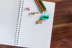 Zwei schärften Bleistift, Bleistiftspitzer und breiteten Notizbuch aus Stockbild