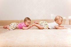 Zwei Schätzchenzwillinge, die nacheinander kriechen Stockfotos