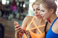 Zwei schöne athletische Blondinen benutzen Smartphone in der Turnhalle Lizenzfreies Stockfoto