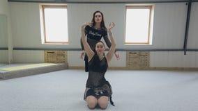 Zwei schöne Bauchtänzerinnen, die im Studio ausbilden, mögen Team stock footage