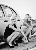 Zwei schöne blonde Mädchen, die nahe defektem Auto und Wartehilfe sitzen Lizenzfreies Stockbild