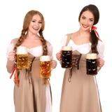 Zwei schöne blonde und Brunettemädchen oktoberfest Bierbierkrug Stockfotografie