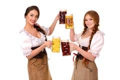 Zwei schöne blonde und Brunettemädchen oktoberfest Bierbierkrug Stockfotos