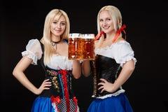Zwei schöne Blondine halten Gläser Bier in den Händen und stehen auf schwarzem Hintergrund im Studio Stockfotografie