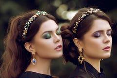 Zwei schöne Brunettefrauen mit einem hellen Farbmake-up, Schmuck, Ring, Ohrring, Augen schlossen Nahaufnahmeporträt von zwei Stockfotos