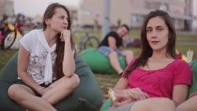 Zwei schöne Brunettemädchenschwestern, die am Park sprechen Sitzende inbean Taschenstühle am Sommertag stock video