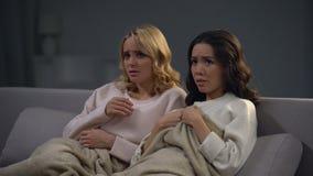 Zwei schöne erschrockene Mädchen, die Horrorfilm nachts, erschreckende Episode aufpassen stock video