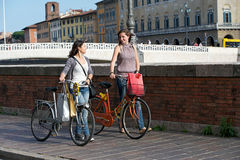Zwei schöne Frauen in der Stadt mit Fahrrädern stockfotografie