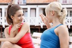 Zwei schöne Freundinnen, die auf Bank stillstehen Stockfotos