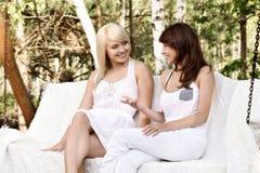 Zwei schöne Freundinnen, die auf Schwingen und der Unterhaltung stillstehen Stockbilder