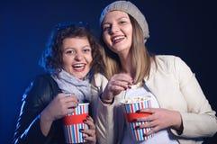 Zwei schöne Freundinnen, die glücklich lachen und aufpassender Film Lizenzfreie Stockfotos